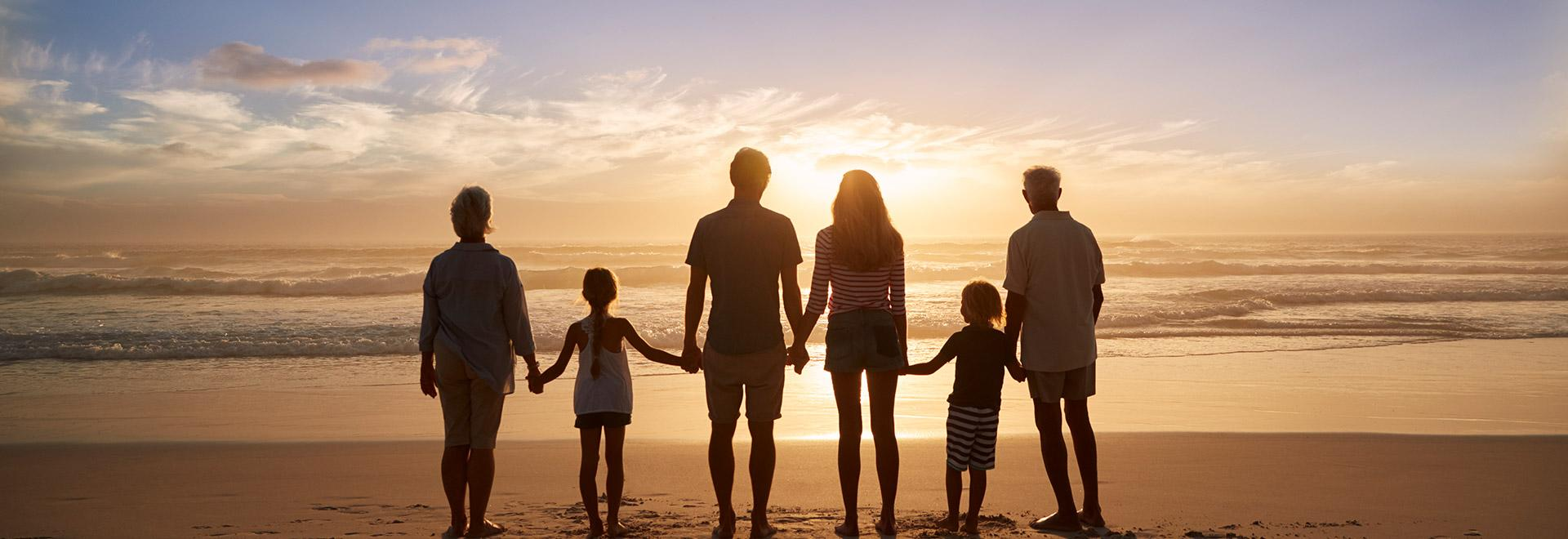 A family holds hands while watching the sunset on their group vacation