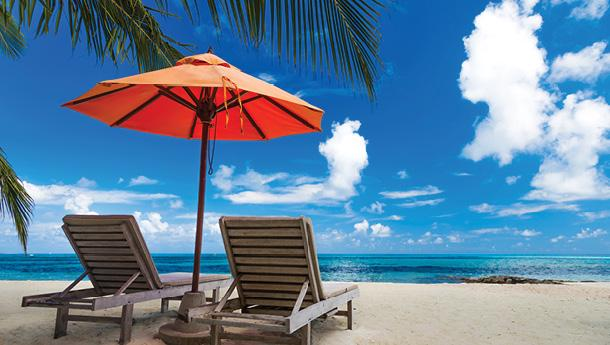 Two lounge chairs on a tropical beach